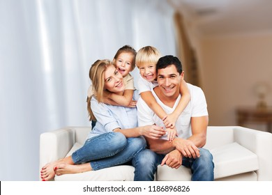 Beautiful smiling family sitting at sofa