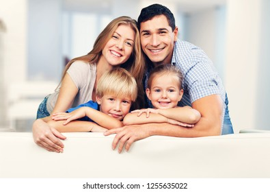 Beautiful smiling family sitting at sofa at home