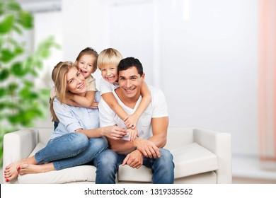 Beautiful smiling family sitting at sofa at home
