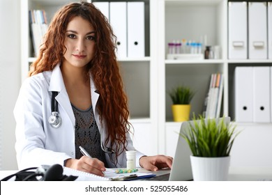 Beautiful smiling female doctor write prescription with silver pen at workplace in office. Panacea and life save, prescribing treatment, legal drug store, take stock, consumption statistics concept