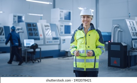 Beautiful Smiling Female Engineer Wearing Safety Vest and Hardhat Holds Safety Goggles. Professional Woman Working in the Modern Manufacturing Factory. Facility with CNC Machinery and robot arm
