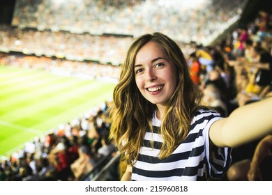 Beautiful smiling female football supporter watching football game and making selfie self-portrait with smartphone at Camp Nou Stadium in Barcelona, Spain