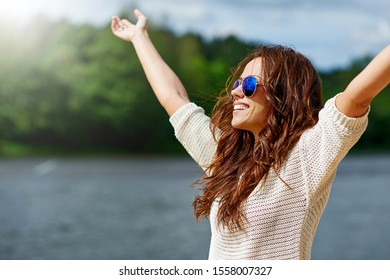 Beautiful smiling female model enjoying freedom with hands raised. Woman in sunglasses outdoor fashion portrait. Close up