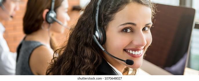 Beautiful smiling female telemarketing customer service agent woking in call center - panoramic banner