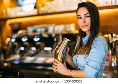 Beautiful smiling girl bartender prepares a cocktail at bar.
