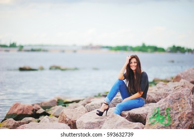 Beautiful smiling girl in black shirt, stylish jeans and shoes on high heels posing while sitting on stones near water.