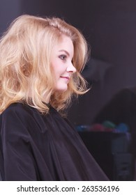 Beautiful smiling girl with blond wavy hair by hairdresser. Young woman in hairdressing beauty salon. Hairstyle.