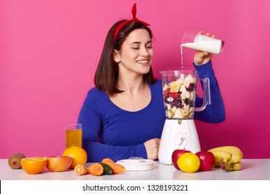 Beautiful smiling girl cooks smoothies in morning. Lots fruit on table. Charming woman adds milk to blender. Goodlooking female makes coktail. Charming lady poses against rose wall in studio.