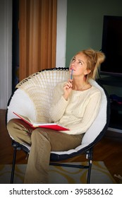 Beautiful smiling girl with diary and pen sitting in the cozy round chair