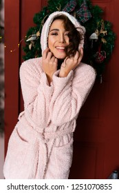 A beautiful smiling girl, dressed in a warm fluffy bathrobe with a hood on her head, stands next to a red door decorated with fir branches and a Christmas tree. Copy space.
