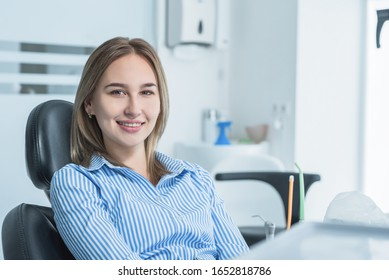 A beautiful, smiling girl examined by a dentist, is sitting in a dental chair