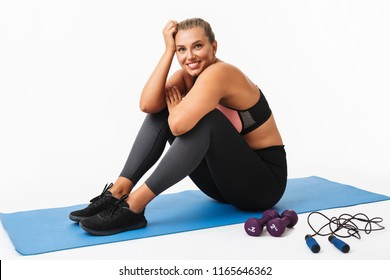 Beautiful smiling girl with excess weight in sporty top and leggings sitting on yoga mat happily looking in camera over white background. Plus size model