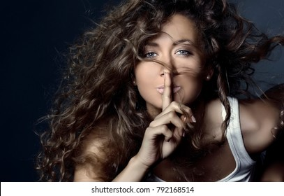 beautiful smiling girl with flying curly hair with a finger at her lips. Keep silence. The secret concept