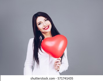 Beautiful smiling girl holding balloon heart in hands. Valentine day concept