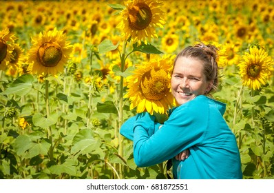Beautiful smiling girl hugging sunflower on summer sunflower field.