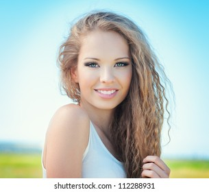 Beautiful smiling girl with long curly hair outdoor