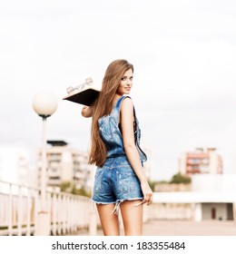 beautiful smiling girl with long legs in jeans short overalls stands with skateboard on shoulder