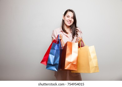 Beautiful smiling girl looks inot a camera holding shopping  boxes