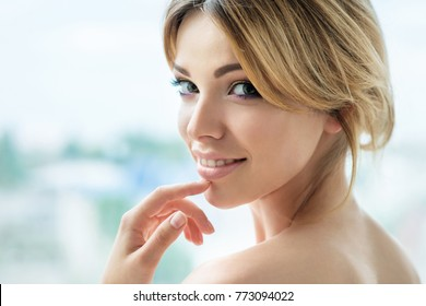 Beautiful  smiling girl with makeup and long lashes front of the window. Beauty, dental and  skincare concept. Spa and wellness. Make up, long hair and lashes. Close up, selective focus.