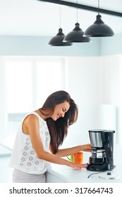 Beautiful smiling girl making coffee for breakfast using filter coffee machine in the kitchen