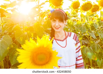 Beautiful smiling girl in national ukrainian blouse embrodery looking to camera on a sunflower field on sunset, backlight