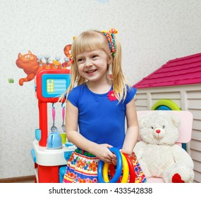 Beautiful smiling girl playing with toys in daycare