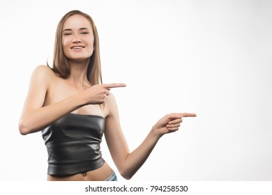 The beautiful smiling girl points a fingers to the empty copy space for your text. Isolated on a white background. Healthy clean leather. Copy space. Advertising and Commercial Design.