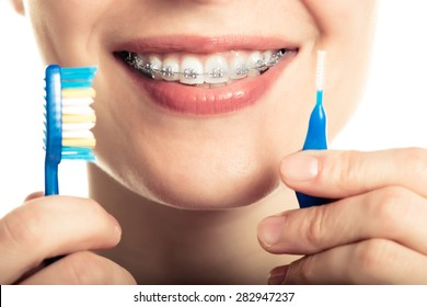 Beautiful smiling girl with retainer for teeth brushing teeth on a white background.