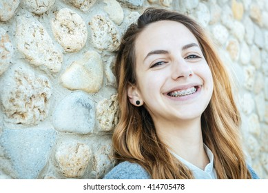 Beautiful smiling girl with retainer for teeth is resting on the outdoors .
