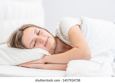 Beautiful smiling girl sleeps in the bedroom at home