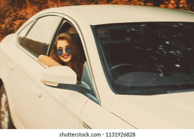 beautiful smiling girl in sunglasses sdriving a car at the autumn streets