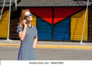 beautiful smiling girl is talking on the phone, space for text
