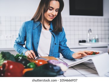 Beautiful smiling girl using digital tablet device searching healthy food recipes, happy smiling brunette girl using tablet pc while cooking vegetarian food in modern kitchen, organic food lifestyle