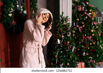 A beautiful smiling girl in a warm fluffy robe, dressed in a hood on her head, stands near the red door, decorated with fir branches and a Christmas tree.