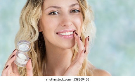 Beautiful smiling girl with wavy hair cares of her lips.  Young blonde woman applying make-up cosmetic SPA product. Model using lip balm or gloss for hydration, nutrition, smoothing balm
