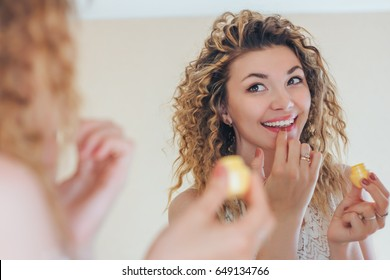 Beautiful smiling girl with wavy hair cares of her lips. Young woman applying make-up cosmetic SPA product. Model using lip balm or gloss for hydration, nutrition, smoothing.
