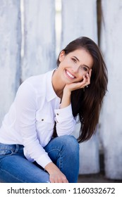 Beautiful smiling girl wearing blank white shirt and jeans posing against street wooden wall. Minimalist urban clothing style, street fashion.