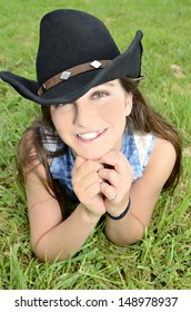 A beautiful smiling girl with western style hat lying in the grass.