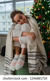 Beautiful smiling girl in a white sweater and warm socks sits wrapped in a warm blanket on a decorated Christmas tree and window behind which there is a cold snowy street.