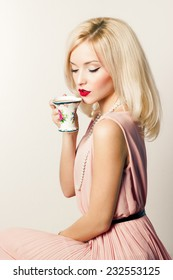 beautiful smiling happy sexy elegant girl with red lipstick in a pink dress in retro style drinks tea coffee from a small mugs