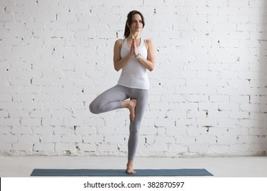 Beautiful smiling happy young woman working out indoors, doing yoga exercise on blue mat, standing in Vrksasana Posture, Tree Pose, full length