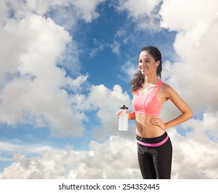 Beautiful smiling healthy woman holding water bottle against blue sky with white clouds