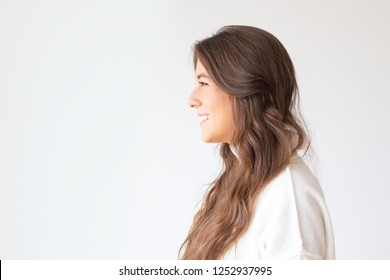 Beautiful smiling Hispanic girl with long hair, side view. Profile portrait of attractive Latin woman smiling and looking aside. Isolated on white. Beauty concept