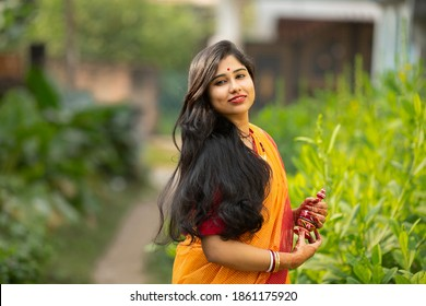 Beautiful smiling Indian bride dressed in Hindu traditional wedding clothes Saree and throwing her hair with green blurry background. Flying hair. Bengali wedding. Kolkata wedding.