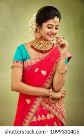 Beautiful smiling Indian bride with jewelry in studio shot.