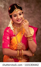Beautiful smiling Indian bride posing  with jewelry in studio shot
