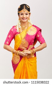 Beautiful smiling Indian bride posing  with jewelry in studio shot on white
