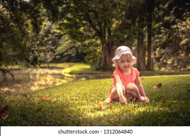 Beautiful smiling kid girl sitting alone on grass in lush green summer park in tree shadow childhood lifestyle