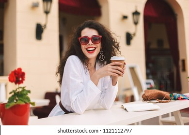 Beautiful smiling lady with dark curly hair in sunglasses standing with cup of coffee to go in hands and happily looking in camera while spending time in summer terrace of cafe