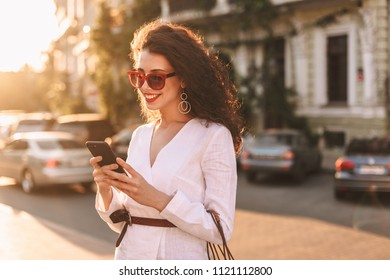 Beautiful smiling lady with dark curly hair in sunglasses and white jacket happily using her cellphone while standing on street